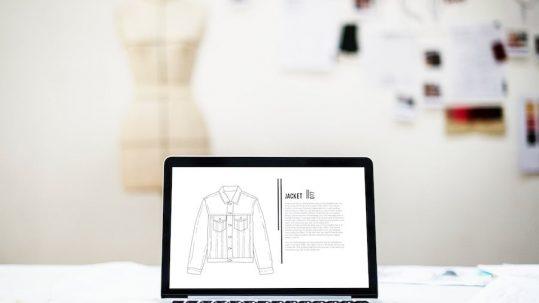 Su un computer si intuisce la descrizione di un capo d'abbigliamento. Sullo sfondo un manichino spoglio.